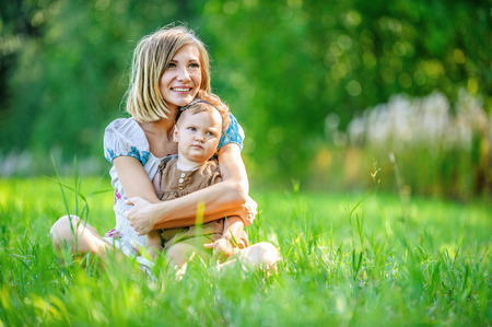 beautiful young mother daughter relaxing sitting grass background summer meadow green grass trees photo