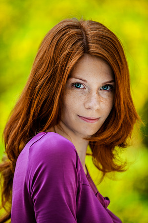 cute teen: Beautiful red-haired smiling young woman in a purple blouse close up. Stock Photo
