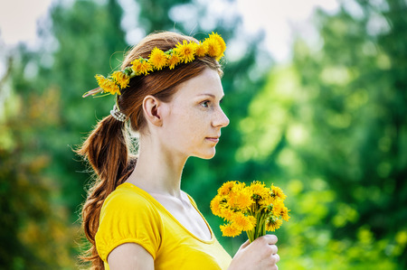 Beautiful red-haired smiling young woman in yellow blouse with a wreath and a bouquet of dandelions on a green background of summer city park.