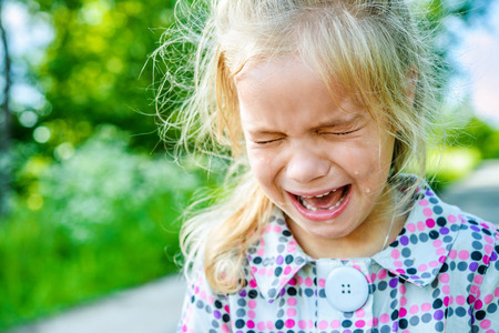 cries: Beautiful sad little girl crying, on summer background. Stock Photo