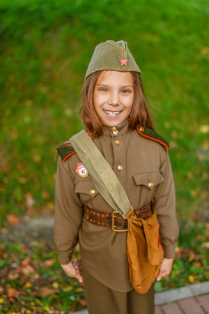 army girl: Little beautiful smiling girl in Soviet military uniforms.