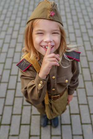 Little beautiful smiling girl in Soviet military uniforms. photo