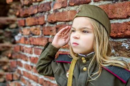 female soldier: Little beautiful girl in Soviet military uniforms. Stock Photo