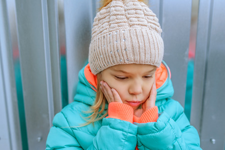knit cap: Beautiful little girl in a pink jacket and knit cap.