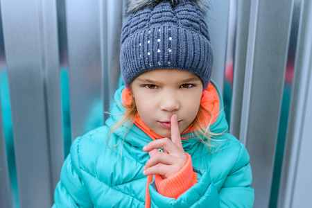 child portrait: The little girl in a blue winter jacket raised a finger to his lips.