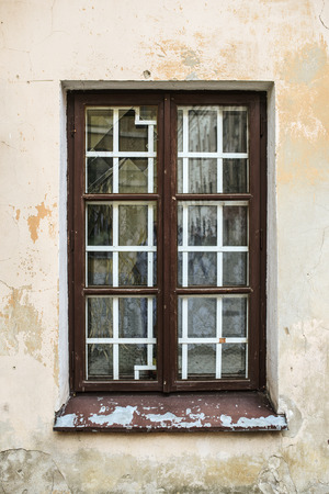Window on an old European building with wrought iron bars.