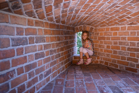 loopholes: Little girl sitting on the fortress wall around the loopholes. Stock Photo