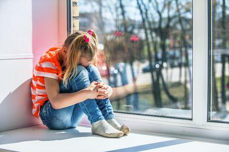 in jeans: La niña en la blusa de color naranja se sienta en el alféizar de una ventana, llorando.