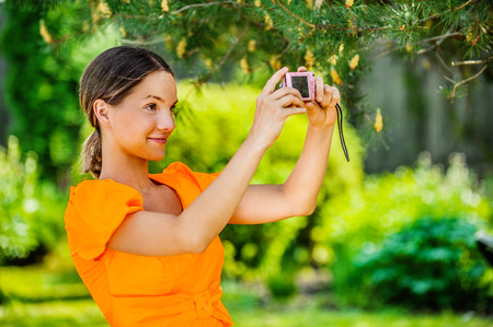 aslant: Portrait of dark-haired smiling beautiful young woman in orange blouse with camera, against green of summer park.