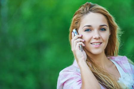 hablando por telefono: largo hermoso parque pelo mujer joven hablando teléfono móvil