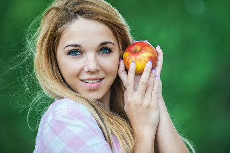 comestible: young beautiful woman long hair park offering red apple