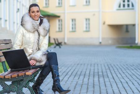 personas sentadas: hermosa mujer sonriente joven en la capa blanca con cuello de piel se sienta en banco y la celebración de ordenador portátil en su regazo. Foto de archivo