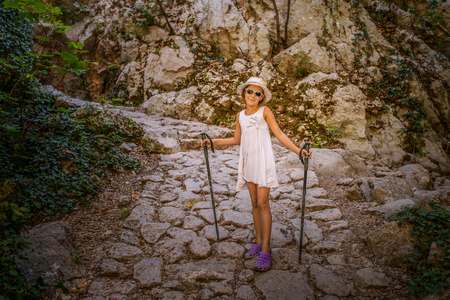 paklenica: Little girl is engaged in Nordic Walking in the mountains of Croatia - in the Great Paklenica. Stock Photo