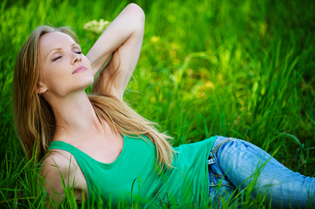 Portrait of beautiful young woman eyes closed lying green grass at summer green park photo