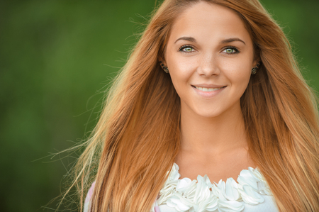 Portrait of beautiful smiling young woman, against green of summer park. photo
