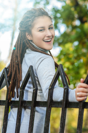 tresses: Young beautiful woman with hairdress dreadlocks close up against green grass.