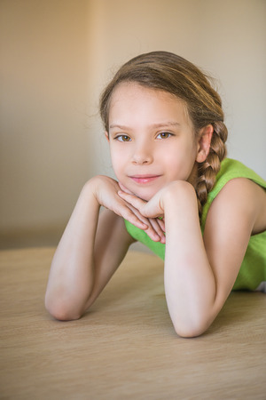 smiling face: Little girl with pigtails sitting at a large table. Stock Photo