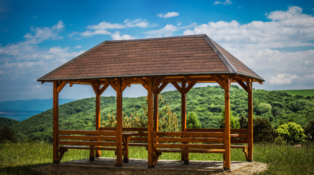 arbor: A wooden gazebo in summer city park.