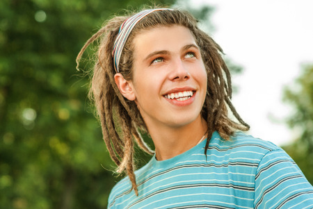 dramatic characters: Young man with dreadlocks against summer garden.