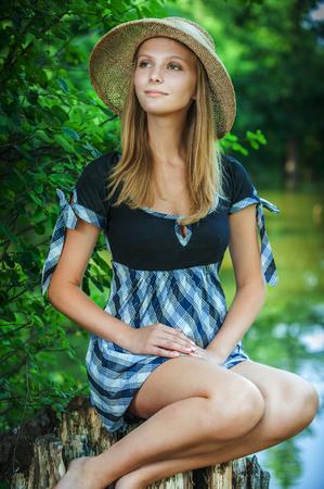 femme romantique: Jeune femme sourit en chapeau de paille sur stub, au parc de la ville d'été.