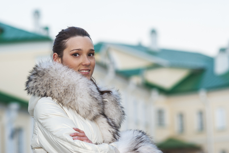 house coats: Young smiling beautiful woman in white coat with fur collar on background of buildings with green roofs.
