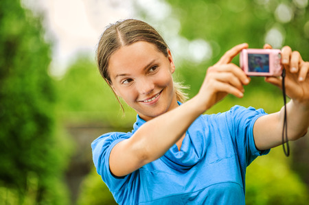 aslant: Portrait of dark-haired smiling beautiful young woman in blue blouse with camera, against green of summer park.