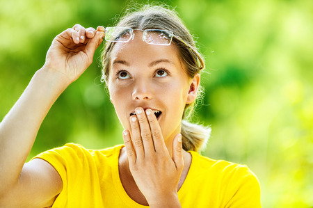 green nature: Dark-haired smiling beautiful young woman in yellow blouse and glasses is surprised, against green of summer park.