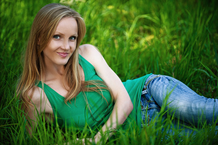 Portrait of young pretty woman sitting on green grass at summer green park photo