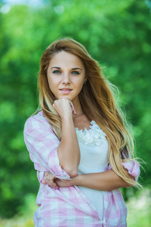 Portrait close up of young beautiful woman, on green background summer nature. photo