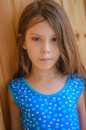 petite fille avec robe: Belle petite fille en robe bleue près de la paroi en bois. Banque d'images