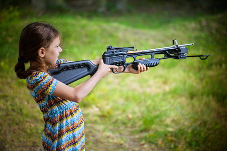 arbalest: Little girl shooting crossbow at summer outdoor shooting range.