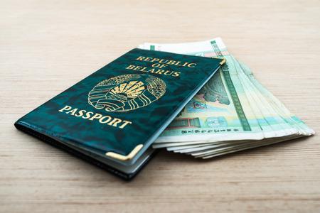 foto carnet: Pasaporte de la Rep�blica de Belar�s en la cubierta verde con rublos bielorrusos extiende sobre la mesa de madera. Foto de archivo