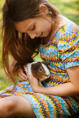 Little girl lying on grass and petting guinea pig.