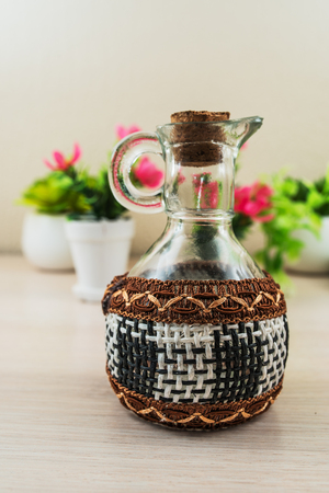 quench: Glass jar with wicker elements on table. Stock Photo