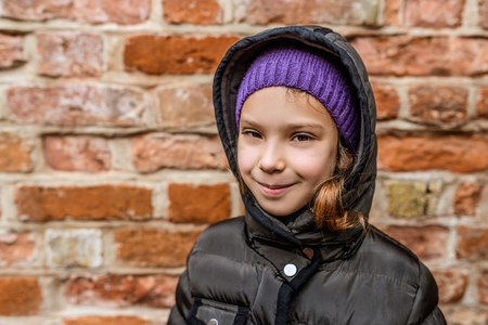 frock coat: Portrait of smiling beautiful little girl close-up, against background of a brick wall. Stock Photo