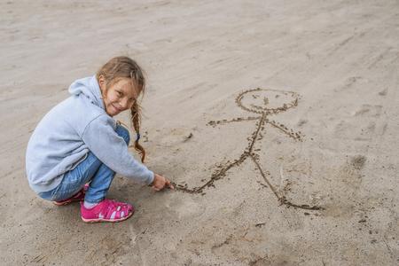small girl: Little cheerful beautiful girl in sweater in sand draws funny man.
