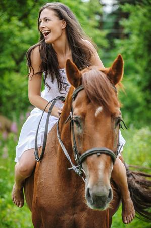 caresses: beautiful young woman park riding horse Stock Photo
