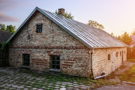 green building: Old brick house in a village in eastern Poland.