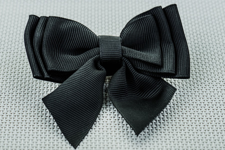 Black bow lies on the gray table. Stock Photo