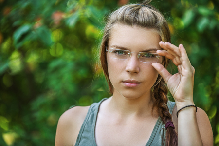 Portrait of beautiful young woman with glasses close up, against green of summer park.