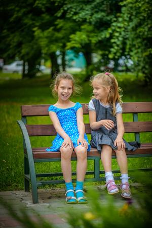 Deux belles petites soeurs souriant assis sur un banc en été parc de la ville verte.