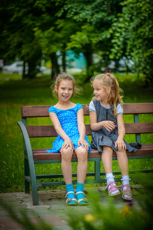 sitting on a bench: Two beautiful smiling little sisters sit on a bench in summer green city park.