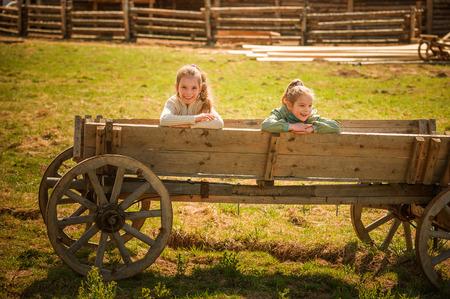 carreta madera: Dos hermanas que se sientan en un viejo vagón de madera en la aldea.