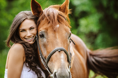 horse laugh: Portrait of young pretty cheerful woman with horse at summer green park.
