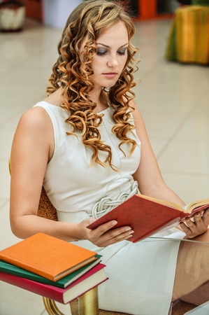 table skirt: serious young woman student sitting table reading book Stock Photo