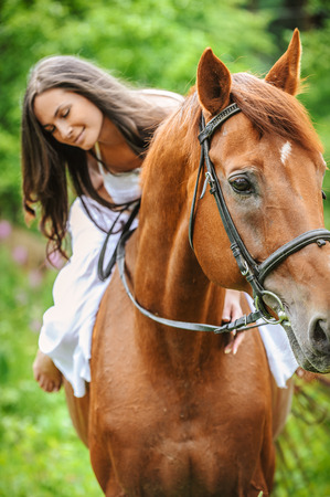girl on horse: Portrait of young beautiful smiling brunette woman wearing white dress riding dark horse at summer green forest. Stock Photo
