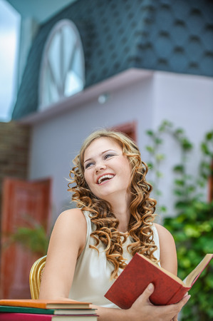 table skirt: smiling young woman student sitting table reading book Stock Photo