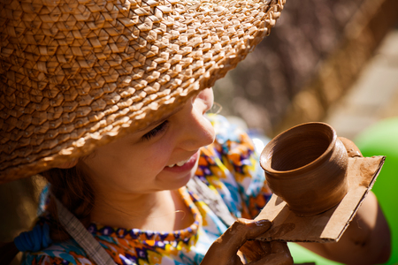 potters wheel: Little girl produced on potters wheel pot. Stock Photo