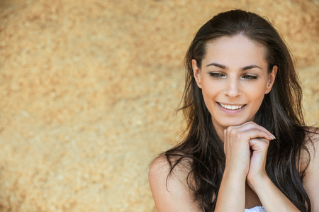 appealing attractive: Portrait of young charming cheerful woman propping up her face against beige background.