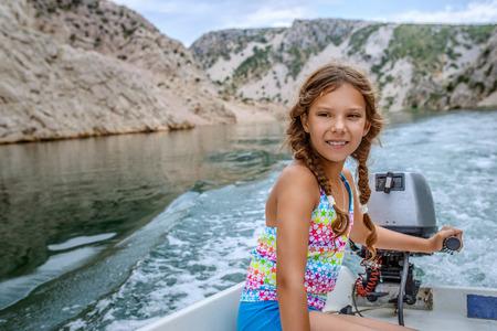 MOTORIZADO: Niña alegre conduce un bote a motor, cerca de la desembocadura del río Zrmanja es un río en el sur de Lika y el norte de Dalmacia, Croacia.